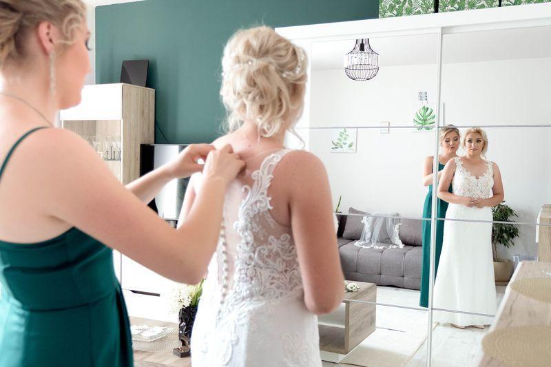 Druhna zapinająca suknię panny młodej